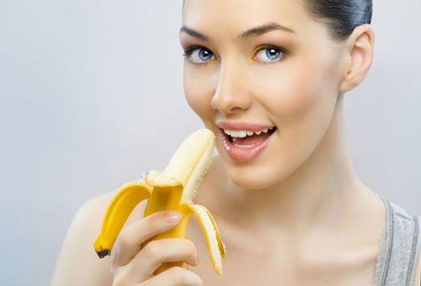 Девушка ест банан