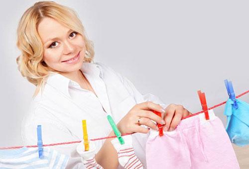 Женщина развешивает постиранные вещи новорожденного