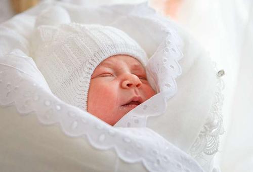 Новорожденная девочка в вязанном чепчике