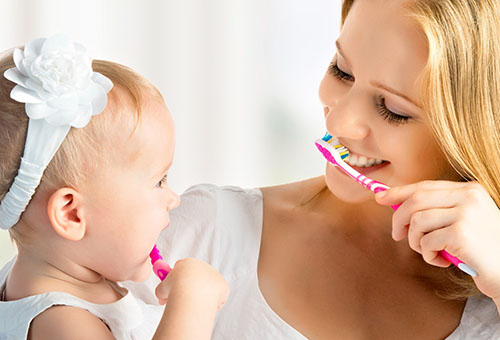 Мама показывает дочке, как чистить зубы