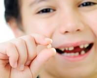 Молочный зуб в руке у мальчика