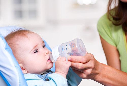 Малыш пьет воду из бутылочки