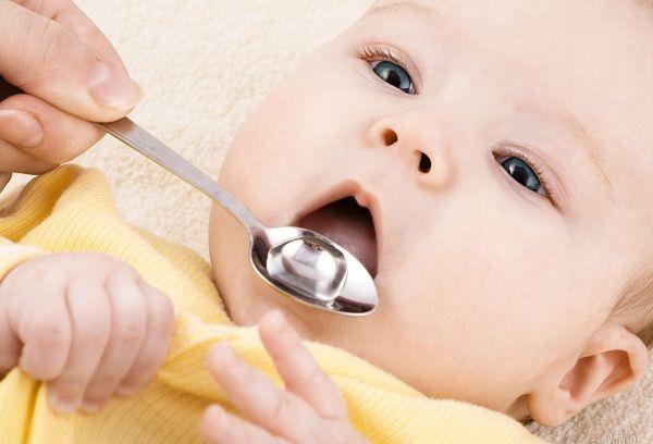 Малыш пьет укропную воду из ложки