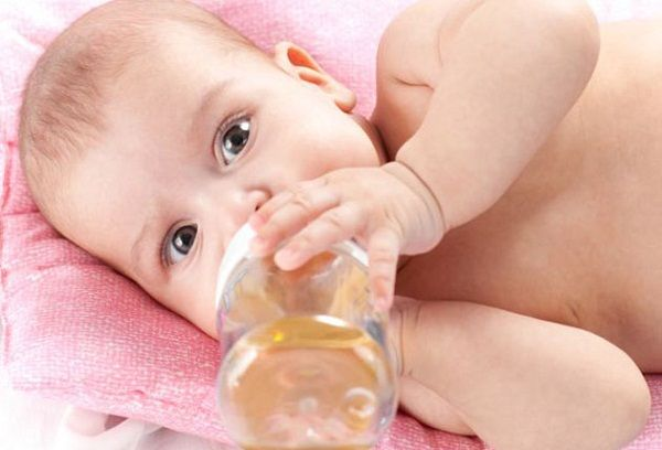 Малыш пьет укропную воду из бутылки