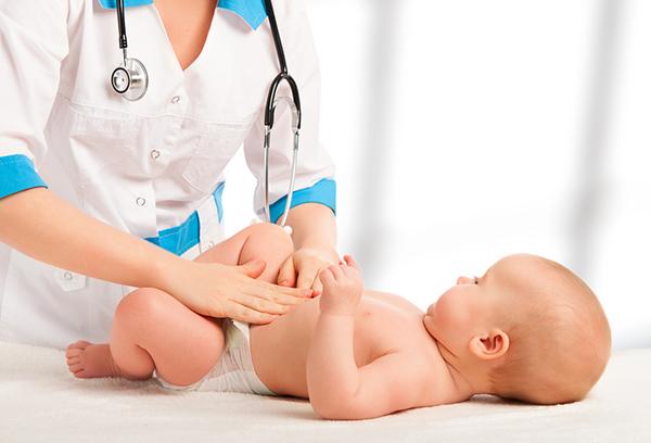 Доктор делает массаж животика малышу