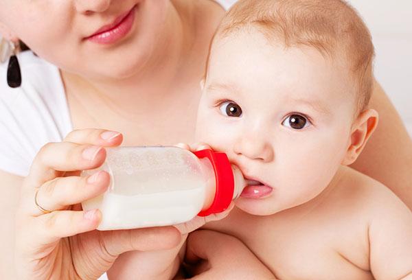 Мама кормит ребенка смесью