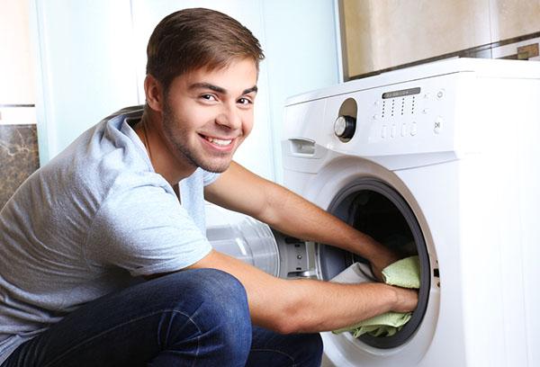 Молодой человек достает вещи из стиральной машины