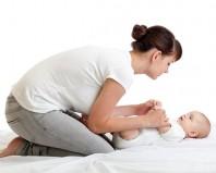 Мама занимается гимнастикой с новорожденным