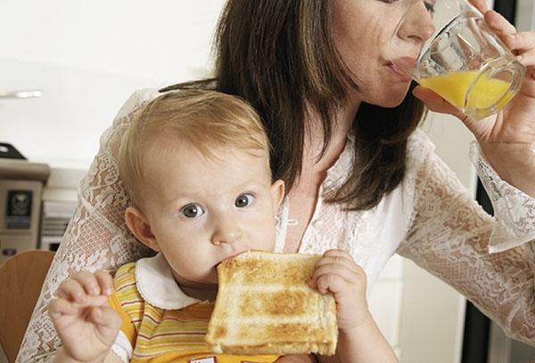Ребенок ест, сидя у мамы на коленях