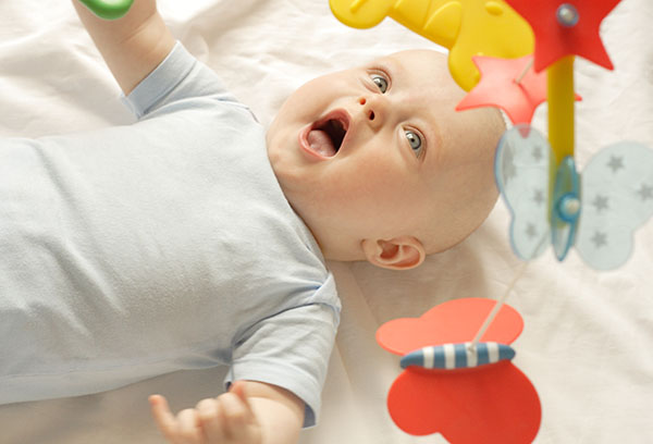 Шестимесячный ребенок в кроватке смотрит на игрушки