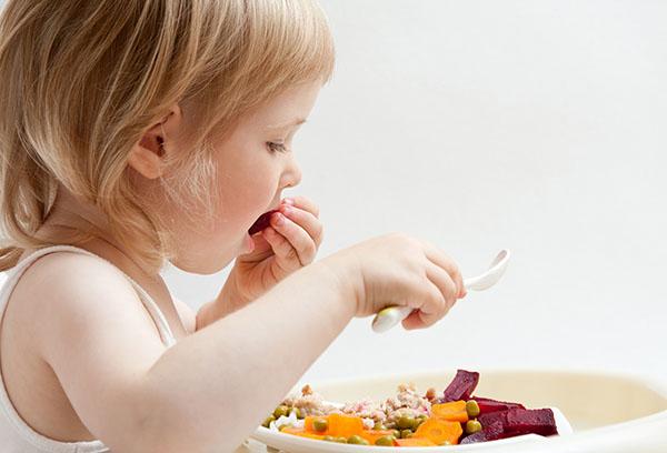 Девочка ест овощи