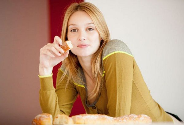 Молодая мама ест хлеб