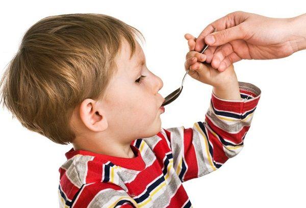 мальчик пьет лекарство с ложки