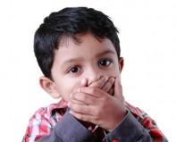 мальчик закрывает рот руками