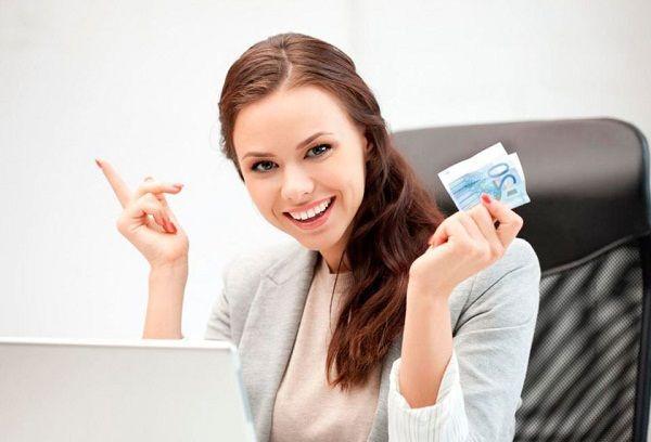 девушка за компьютером с деньгами в руке