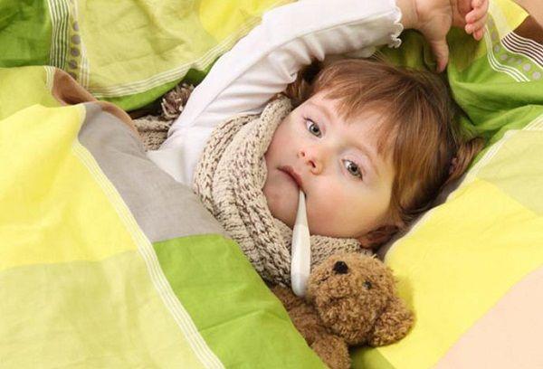 ребенок в кровати с градусником во рту
