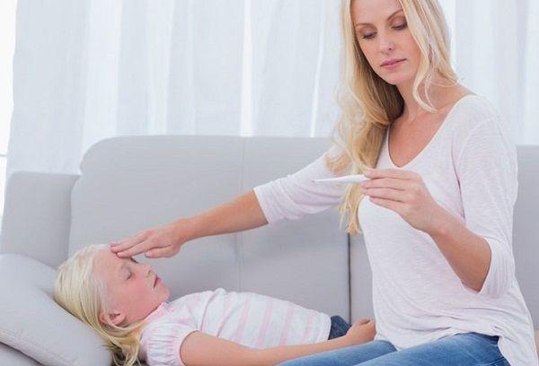 женщина измеряет температуру девочке