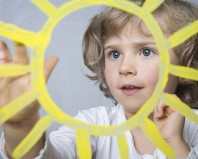 Ребенок рисует солнце на стекле