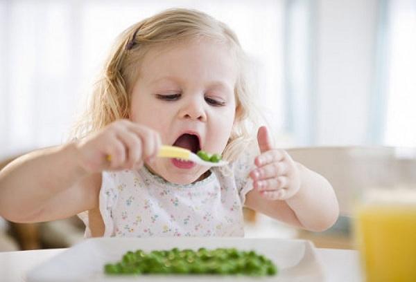 девочка кушает зеленый горошек