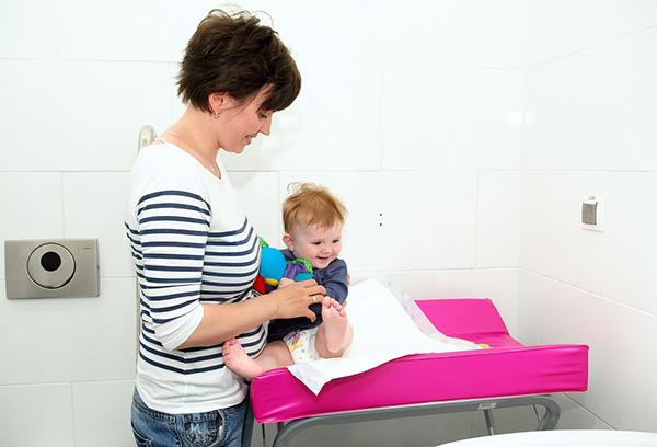 Мама проверяет памперс малыша