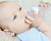 Младенец пьет воду из бутылочки