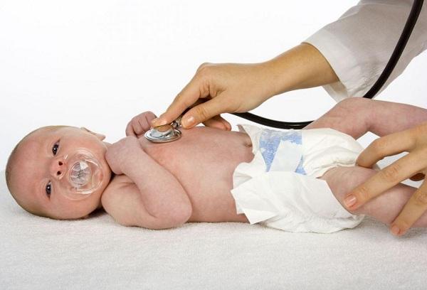 врач слушает биение сердца новорожденного