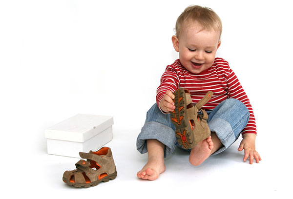 Ребенок надевает сандалии