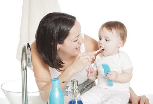 мама обучает ребенка чистить зубки