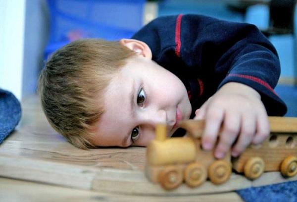 мальчик играет игрушкой