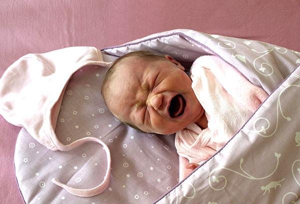 Новорожденная девочка плачет