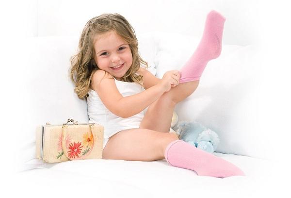 девочка одевает розовые носки