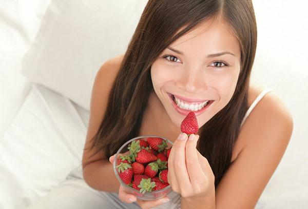 Девушка ест клубнику