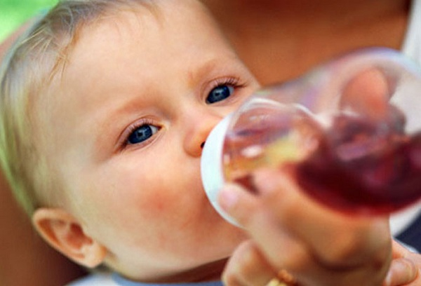 ребенок пьет компот из бутылочки