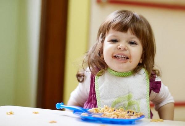 двухлетняя девочка обедает
