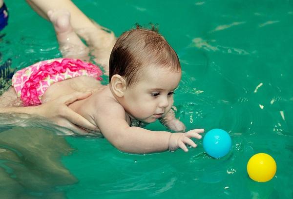ребенок в бассейне играет с мячом
