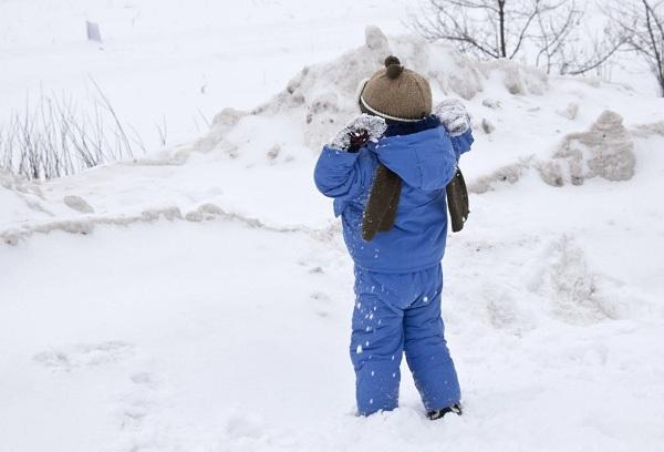 мальчик играет на улице на снегу