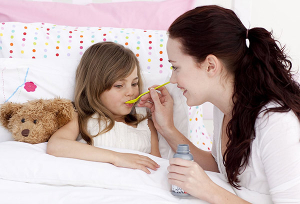 Мама дает дочке лекарство при ОРВИ