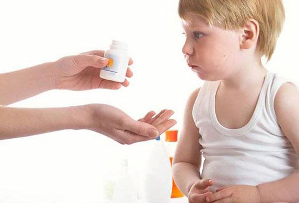 Женщина дает лекарство ребенку