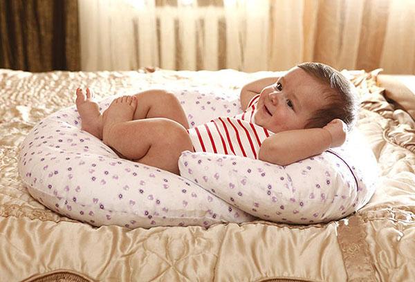 Ребенок лежит на подушке для кормления