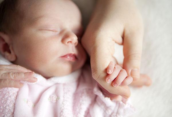 Спящий малыш держит мамину руку