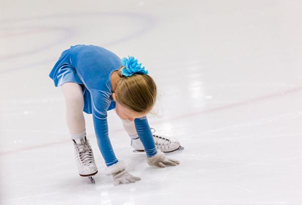 Девочка учится кататься на коньках
