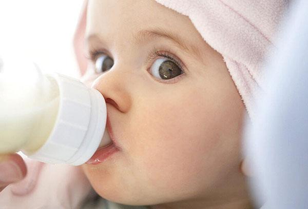 Малыш ест смесь из бутылочки