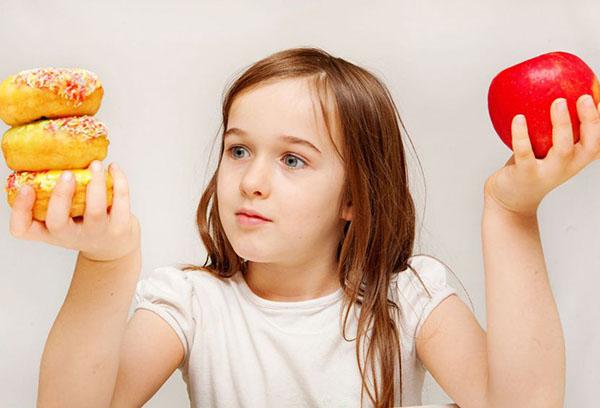 Девочка выбирает между выпечкой и яблоком