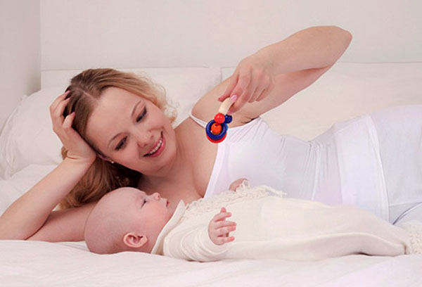 Мама показывает младенцу погремушку