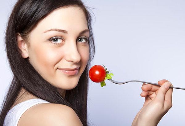 Женщина ест помидор