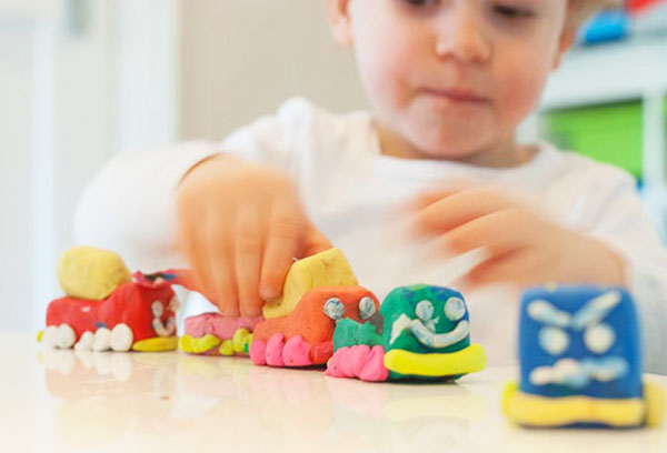 Ребенок лепит паровозик из пластилина
