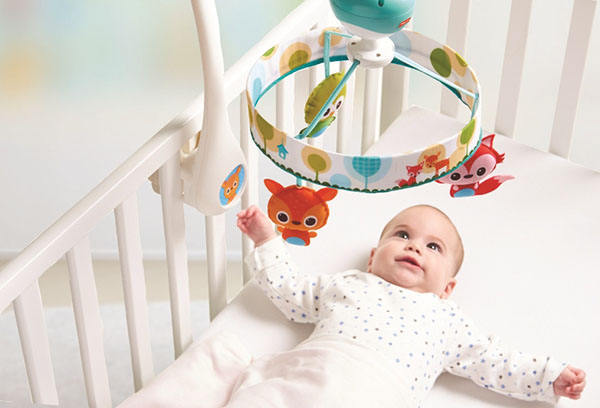 Малыш смотрит на мобиль в кроватке