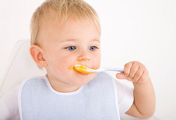 Ребенок ест тыквенную кашу
