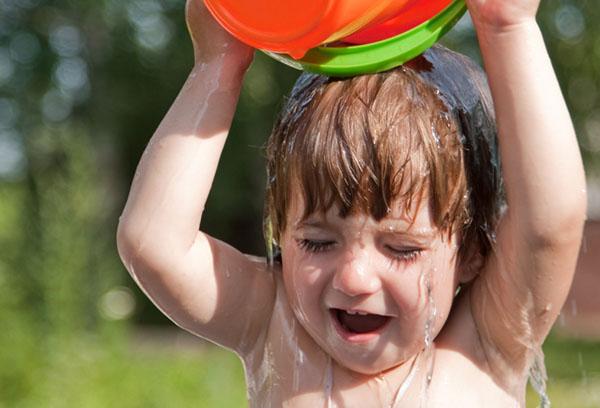 Ребенок обливается водой на улице