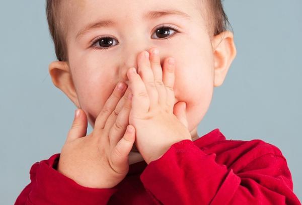 Ребенок прикрывает рот руками